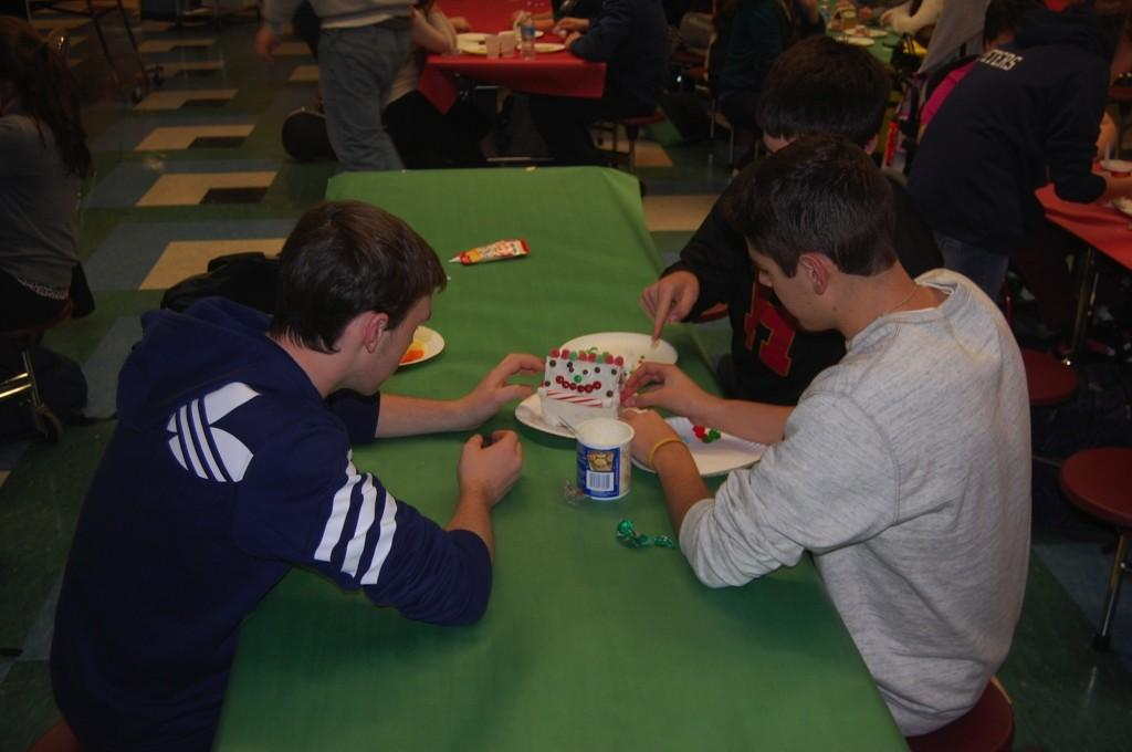 Seniors Will O'Reilly and Corey Cavaliere decorate a gingerbread house.