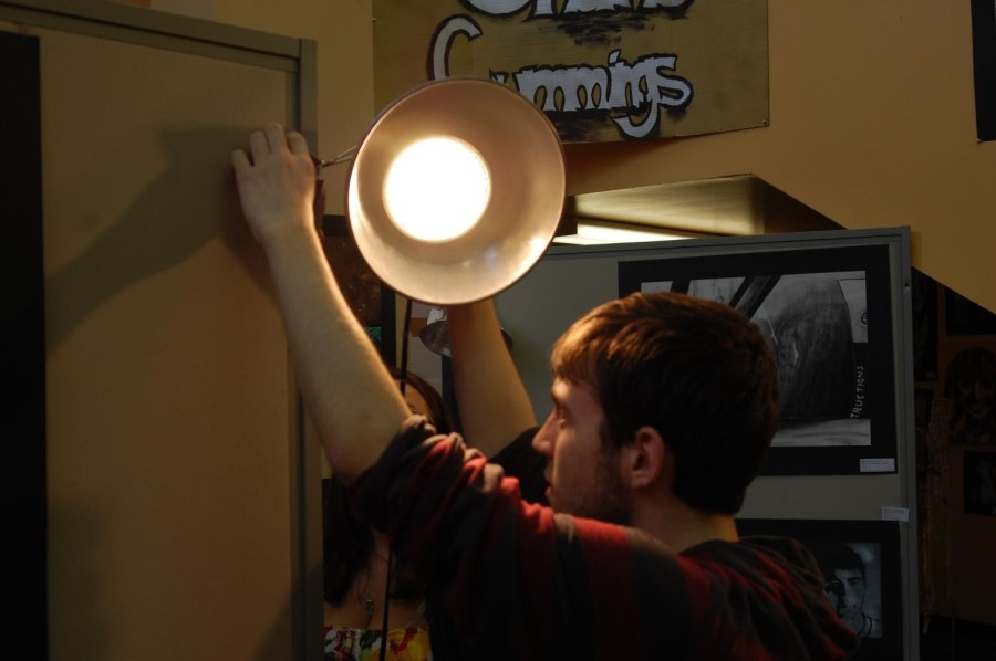 Senior Shane Cummings adjusts a lighting fixture for his art display Friday afternoon.