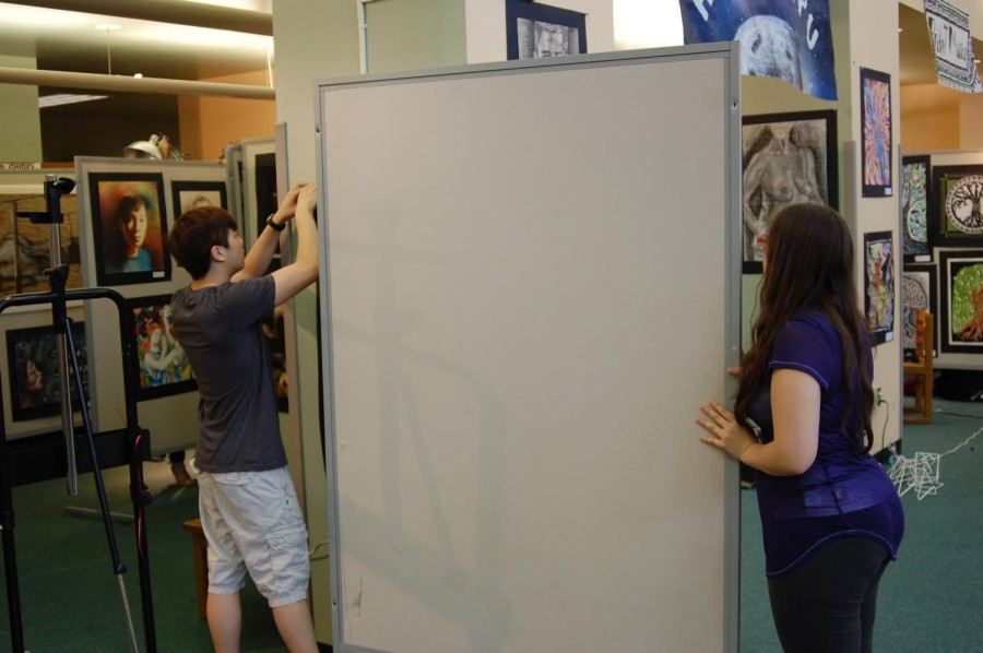 Senior Chris Lee and Junior Skylar Forrest move a display board into place for his section of the Into the Amazon.