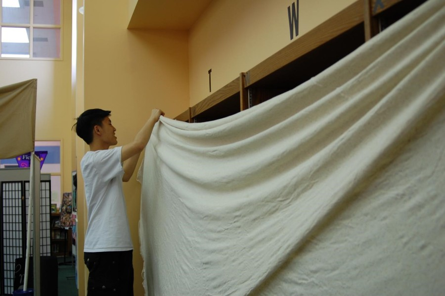 Volunteer Art student Peter Hua hangs a curtain to block out the books in the library to help viewers focus on the art and preserve the original image of the library.