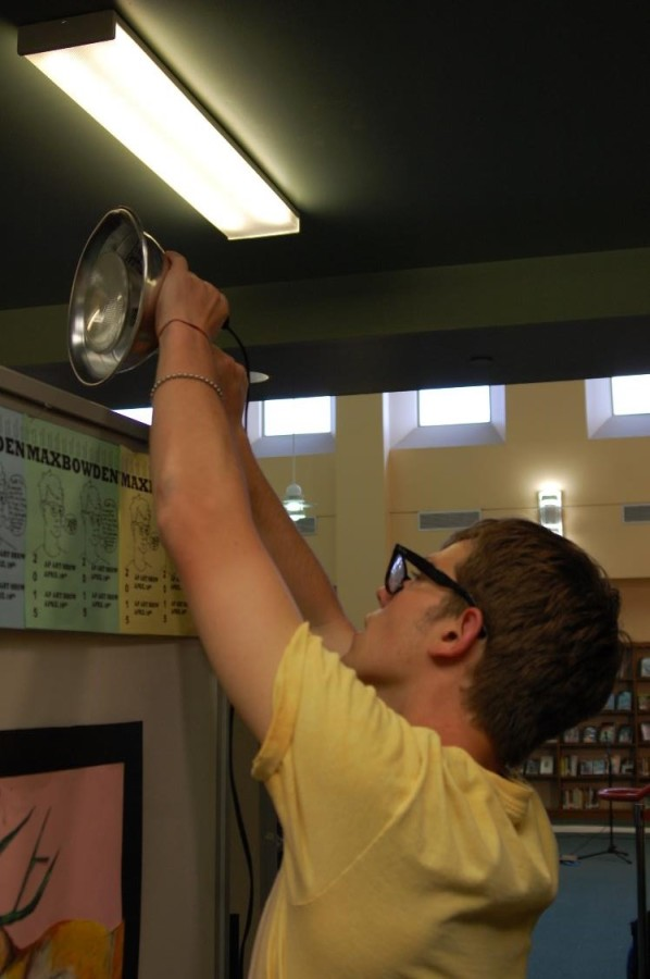 Senior Max Bowden hangs a light for his portion of the show. Bowden's section of the show is right at the entrance of the library.
