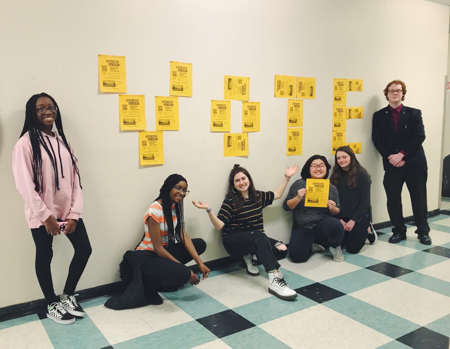 Members of the Young Democrats Club pose in front of their VOTE display.