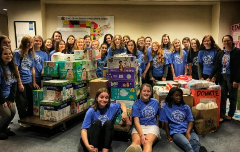 "Pictured sitting (from left to right) are the Diaper Dry've officers Anabel Keagy, Abigail Wright, and Jade May. Surrounding them are the sponsor Tricia Dyal, and the members preparing for the ""Stuff the Bus"" campaign."