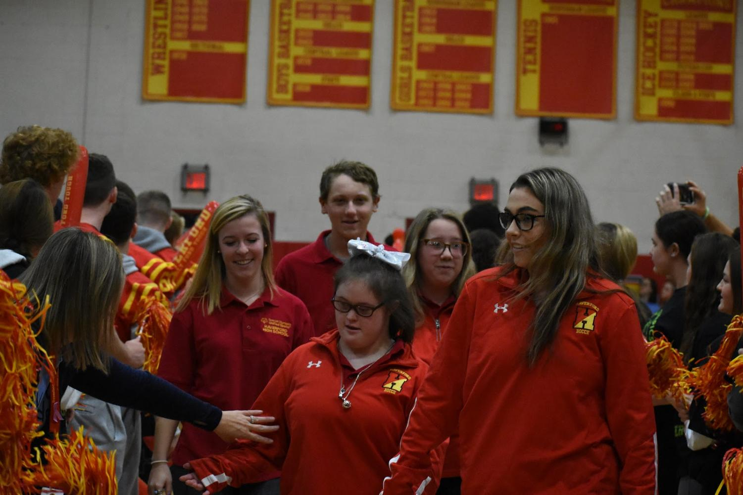 Pictured from left to right are Sarah Goeckel, David Gibson, Molly Warren, Annie Gable, and Meaghan Hennessy entering the Juenger Gymnasium while being cheered on by football players and cheerleaders.