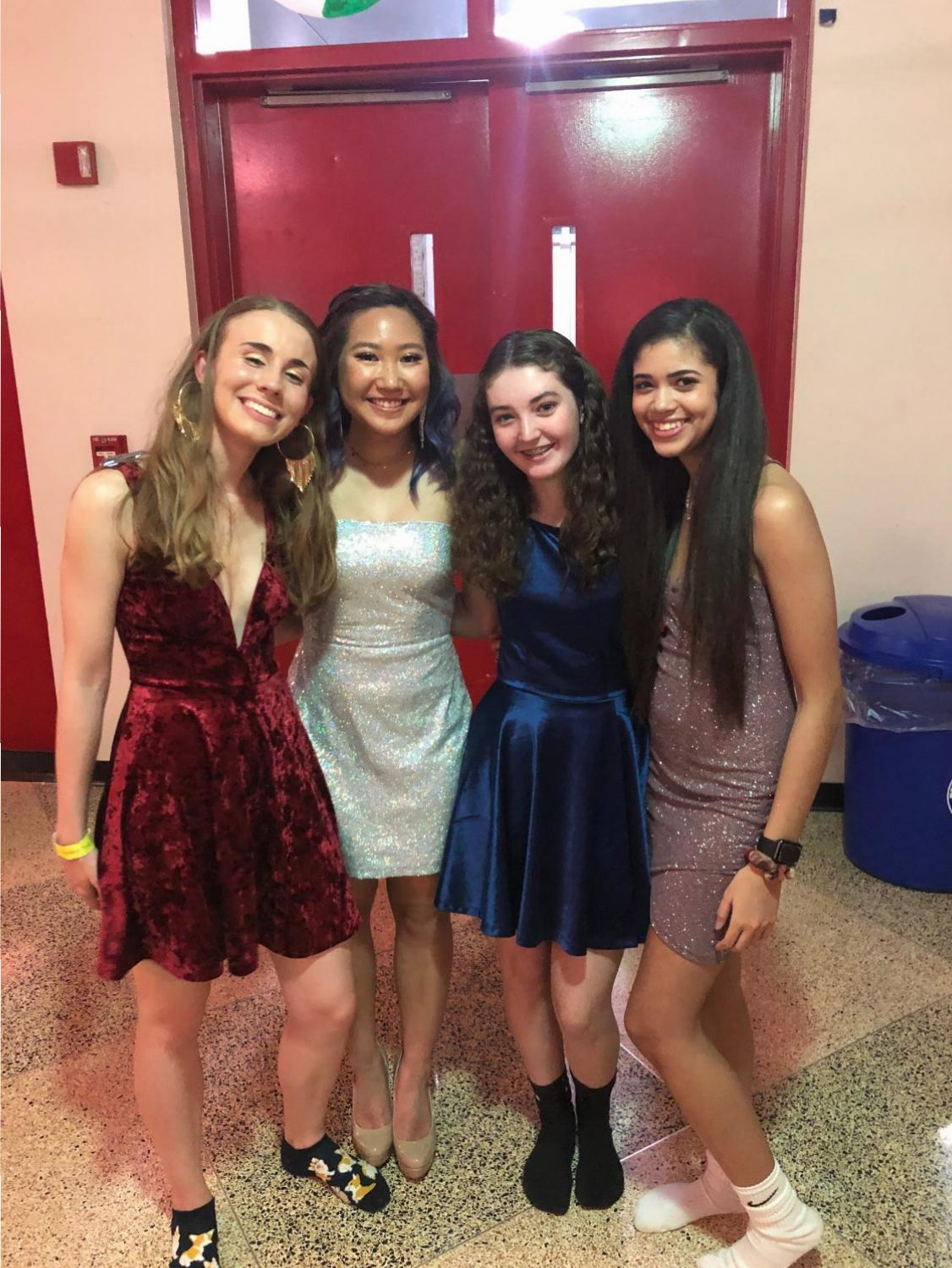 Attending the Homecoming Dance, Sophia Carr, Seryna Chung, Kiera Dowdell, and Taylor Pickering take a break from dancing to mingle in the lobby.