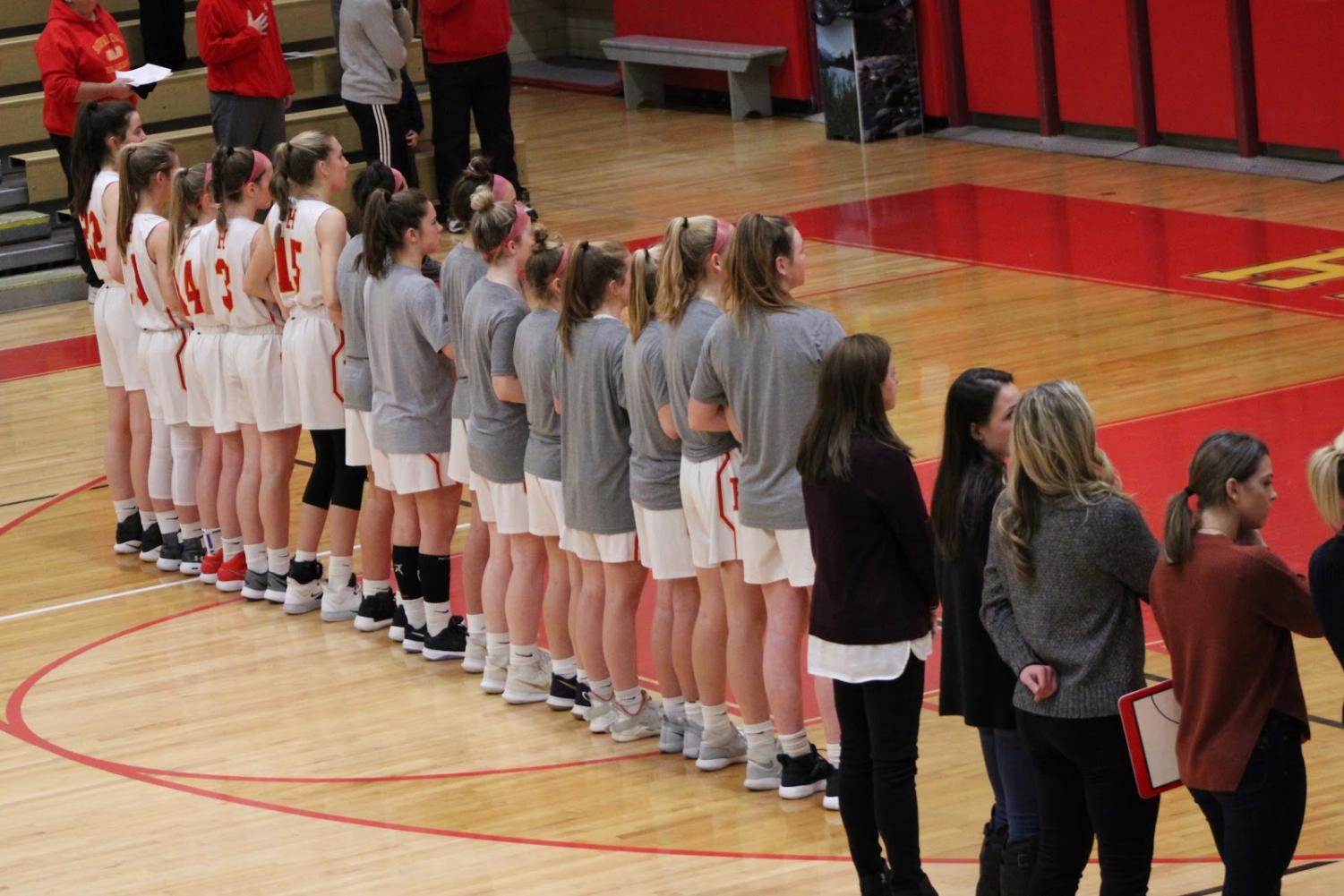 The Lady Fords line up during the pre-game singing of the National Anthem.