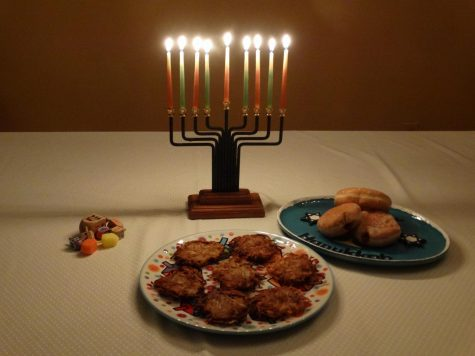 A menorah is lit, framed by the symbols of Hanukkah: Dreidels, Latkes, and Sufganiyot.
